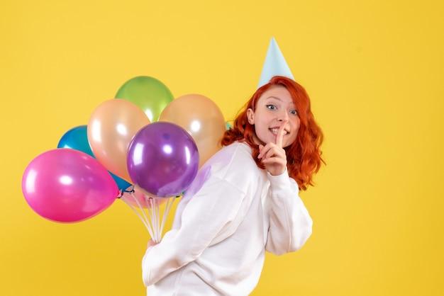 Vista frontal joven mujer escondiendo lindos globos de colores sobre un fondo amarillo año nuevo color emoción regalo niño mujer