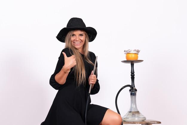 Vista frontal de la joven mujer fumando narguile y sonriendo en la pared blanca