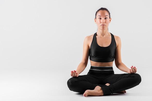 Vista frontal joven mujer meditando