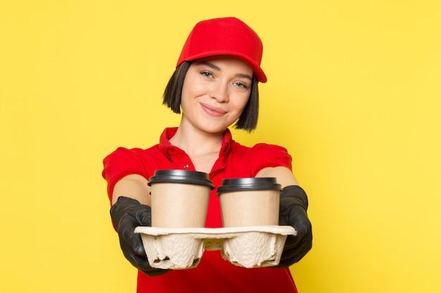 Una vista frontal joven mujer mensajero en rojo uniforme guantes negros y gorra roja con tazas de café