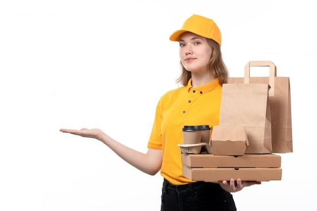 Una vista frontal joven mujer mensajero trabajadora del servicio de entrega de alimentos con cajas de pizza paquetes de alimentos y tazas de café sonriendo en blanco
