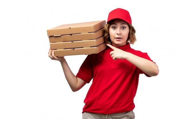 Una vista frontal joven mujer mensajero trabajadora del servicio de entrega de alimentos con entrega de comida cajas de pizza en blanco