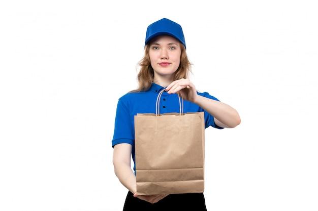 Una vista frontal joven mujer mensajero trabajadora del servicio de entrega de alimentos con paquete de entrega en blanco