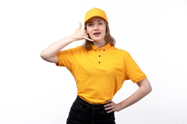 Una vista frontal joven mujer mensajero trabajadora del servicio de entrega de alimentos sonriendo mostrando teléfono hablar pose en blanco
