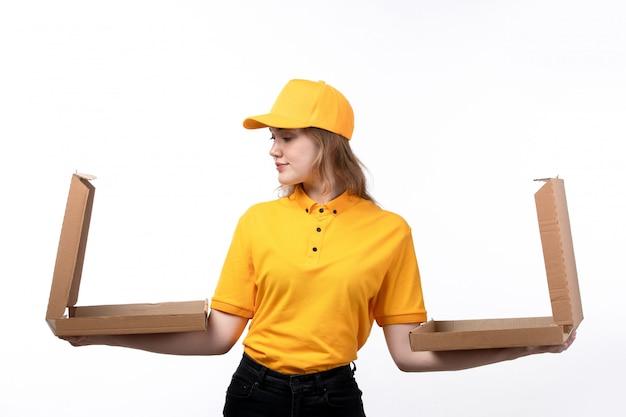 Una vista frontal joven mujer mensajero trabajadora del servicio de entrega de alimentos sonriendo sosteniendo cajas de pizza en blanco