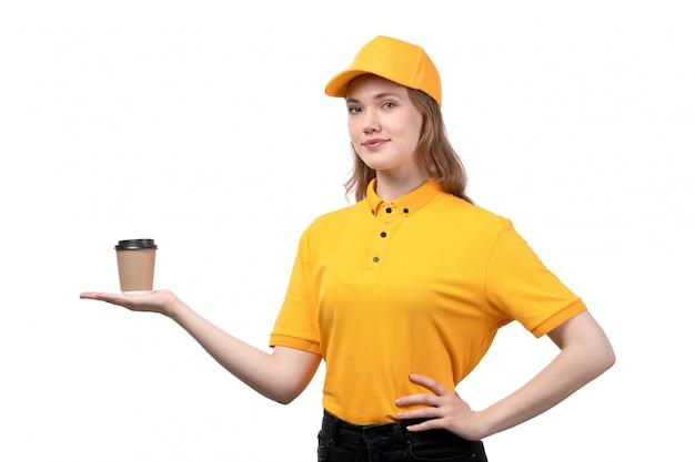 Una vista frontal joven mujer mensajero trabajadora del servicio de entrega de alimentos sonriendo sosteniendo la taza con café en blanco