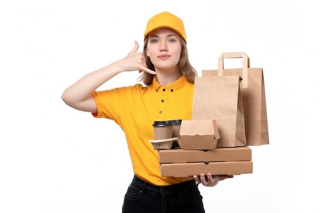 Una vista frontal joven mujer mensajero trabajadora del servicio de entrega de alimentos sosteniendo tazas de café paquetes de alimentos mostrando señal de llamada telefónica en blanco