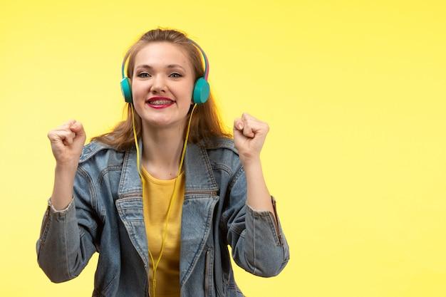 Una vista frontal joven mujer moderna en camisa amarilla pantalón negro y abrigo de jean con auriculares de colores escuchando música posando