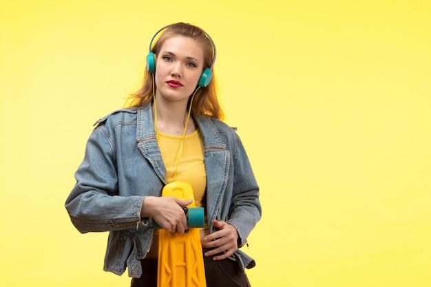 Una vista frontal joven mujer moderna en camisa amarilla pantalón negro y abrigo de jean sosteniendo patineta con auriculares de colores