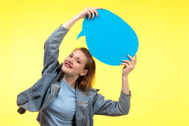 Una vista frontal joven mujer moderna en camisa azul pantalón negro y abrigo de jean posando feliz expresión sonriente sosteniendo cartel de papel azul
