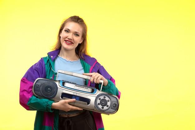 Una vista frontal joven mujer moderna en camisa azul pantalón negro chaqueta colorida sonriendo posando con grabadora