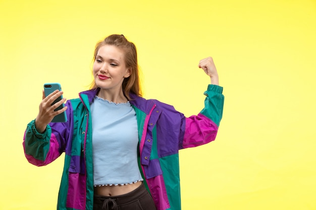 Una vista frontal joven mujer moderna en camisa azul pantalón negro chaqueta colorida sonriendo posando usando teléfono flexionando