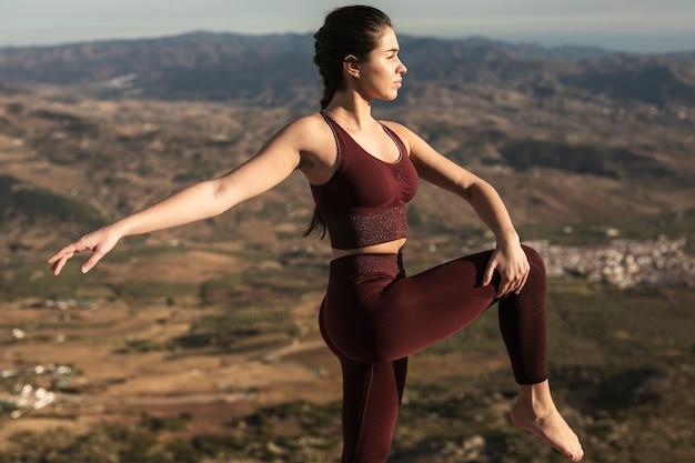 Vista frontal joven mujer practicando yoga