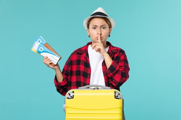 Vista frontal joven mujer sosteniendo billetera con boletos en el espacio azul