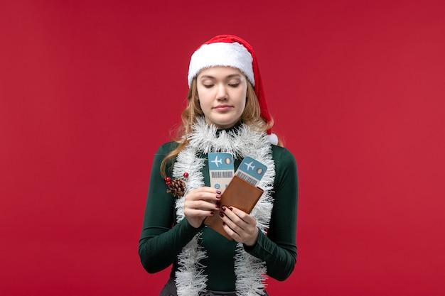Vista frontal joven mujer sosteniendo boletos sobre fondo rojo.