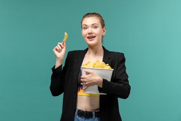 Vista frontal joven mujer sosteniendo y comiendo patatas fritas viendo la película en la superficie azul