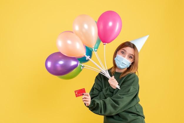 Vista frontal joven mujer sosteniendo globos de colores y tarjeta bancaria