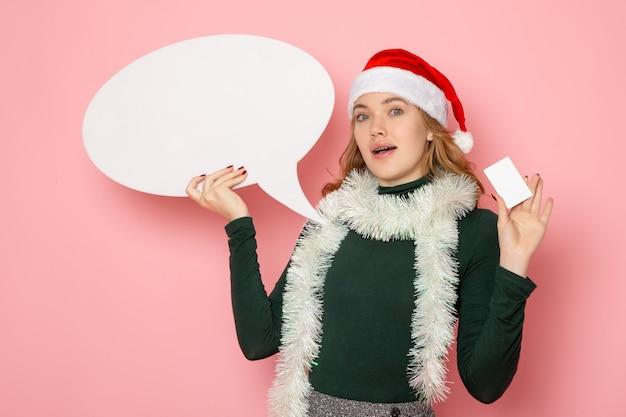 Vista frontal joven mujer sosteniendo gran cartel blanco y tarjeta bancaria en modelo de pared rosa vacaciones navidad año nuevo colores emoción
