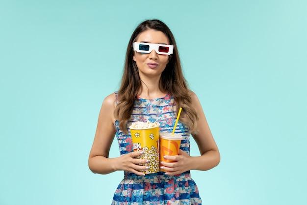 Vista frontal joven mujer sosteniendo palomitas de maíz bebida en d gafas de sol en el escritorio azul