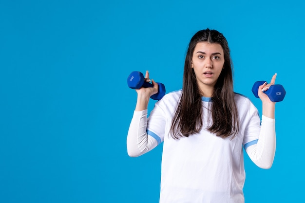 Vista frontal joven mujer sosteniendo pesas azules