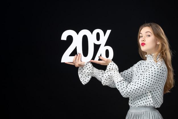 Vista frontal joven mujer sosteniendo porcentaje de descuento de escritura sobre pared negra