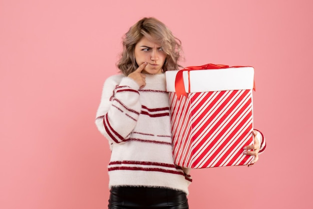 Vista frontal joven mujer sosteniendo presente de navidad con cara confundida
