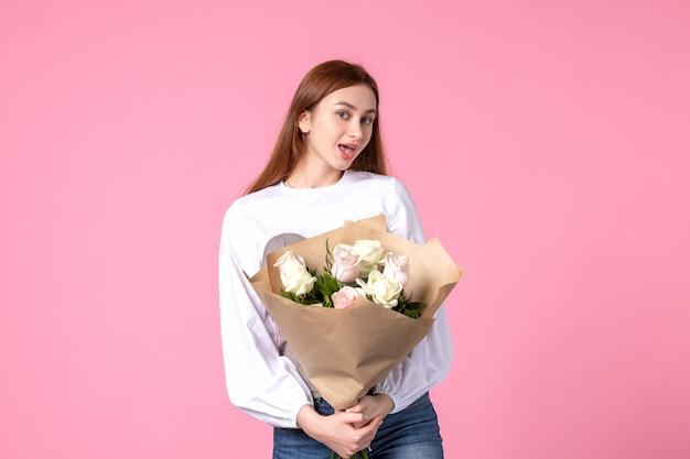 Vista frontal joven mujer sosteniendo ramo de rosas hermosas en rosa