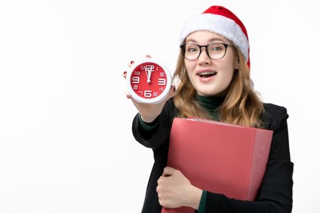 Vista frontal joven mujer sosteniendo reloj con archivos en la pared blanca lección libro de niña
