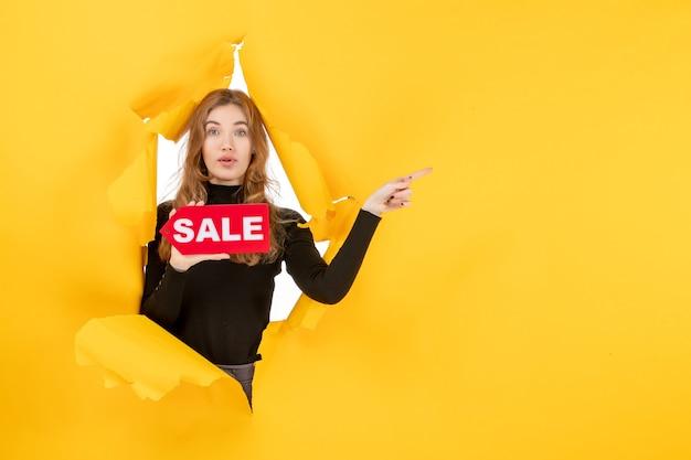 Vista frontal joven mujer sosteniendo rojo venta escrito en pared amarilla