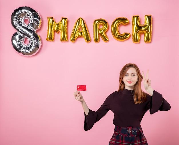 Vista frontal joven mujer sosteniendo tarjeta bancaria en fiesta rosa día de la mujer presente de vacaciones compras