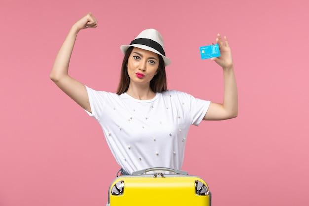 Vista frontal joven mujer sosteniendo tarjeta bancaria flexionando en pared rosa mujer viaje viaje de verano