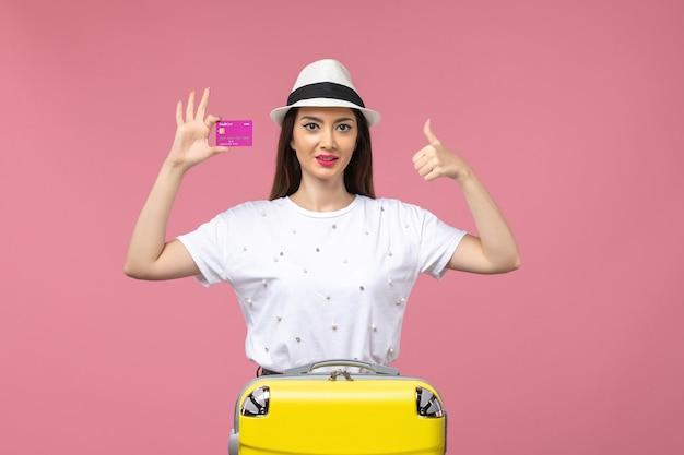 Vista frontal joven mujer sosteniendo tarjeta bancaria en pared rosa claro emociones mujer viaje verano