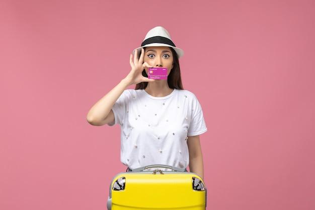 Vista frontal joven mujer sosteniendo una tarjeta bancaria en la pared rosa claro viaje dinero color vacaciones