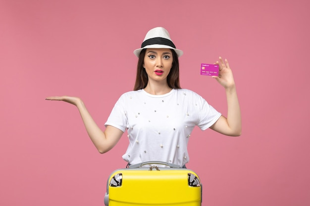 Vista frontal joven mujer sosteniendo tarjeta bancaria en pared rosa claro viaje mujer vacaciones dinero