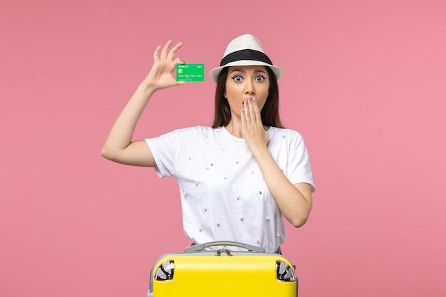 Vista frontal joven mujer sosteniendo tarjeta bancaria en pared rosa claro viaje de verano emociones mujer