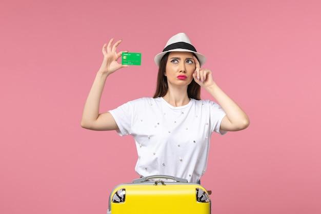 Vista frontal joven mujer sosteniendo tarjeta bancaria en pared rosa emociones mujer de viaje de verano