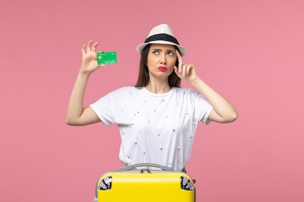 Vista frontal joven mujer sosteniendo tarjeta bancaria en una pared rosa emociones viaje de mujer de verano