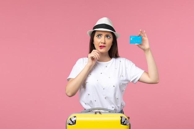 Vista frontal joven mujer sosteniendo tarjeta bancaria en pared rosa mujer viaje emociones de verano