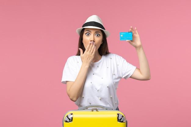 Vista frontal joven mujer sosteniendo tarjeta bancaria en la pared rosa mujer viaje verano emoción