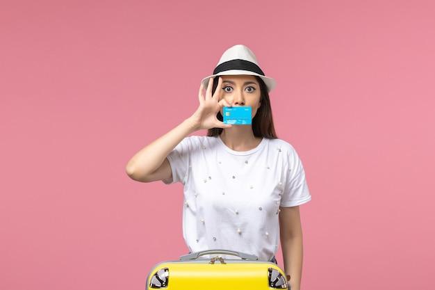 Vista frontal joven mujer sosteniendo tarjeta bancaria en la pared rosa mujer viaje viaje de verano