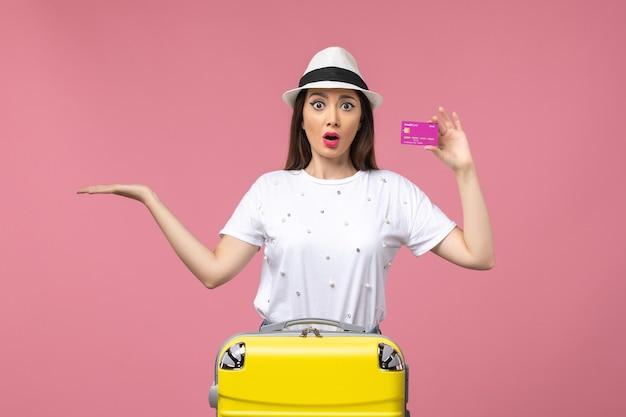 Vista frontal joven mujer sosteniendo tarjeta bancaria en la pared rosa vacaciones dinero mujer viaje