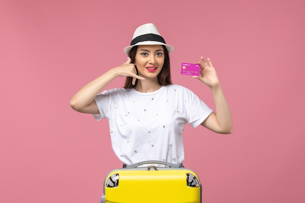 Vista frontal joven mujer sosteniendo tarjeta bancaria en la pared rosa vacaciones mujer viaje dinero