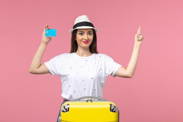 Vista frontal joven mujer sosteniendo tarjeta bancaria en pared rosa viaje mujer emoción de verano