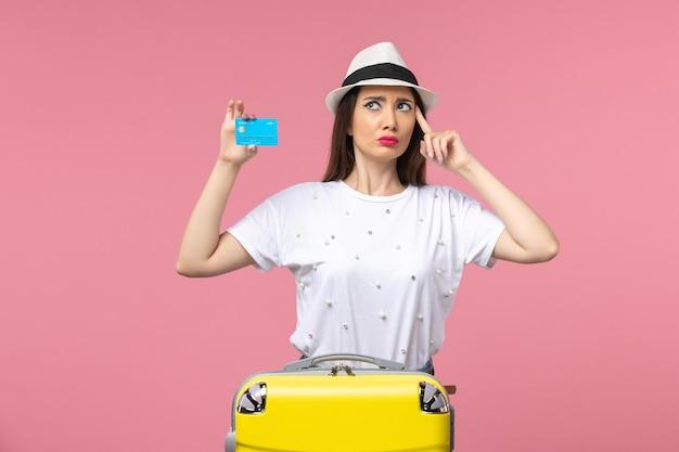 Vista frontal joven mujer sosteniendo tarjeta bancaria en la pared rosa viaje mujer emociones de verano