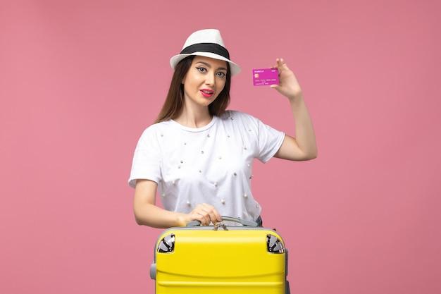Vista frontal joven mujer sosteniendo tarjeta bancaria en la pared rosa viaje vacaciones mujer dinero