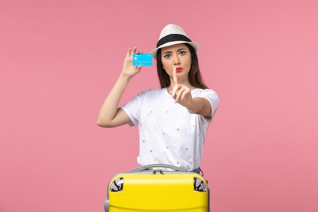 Vista frontal joven mujer sosteniendo tarjeta bancaria en pared rosa viaje verano emoción mujer
