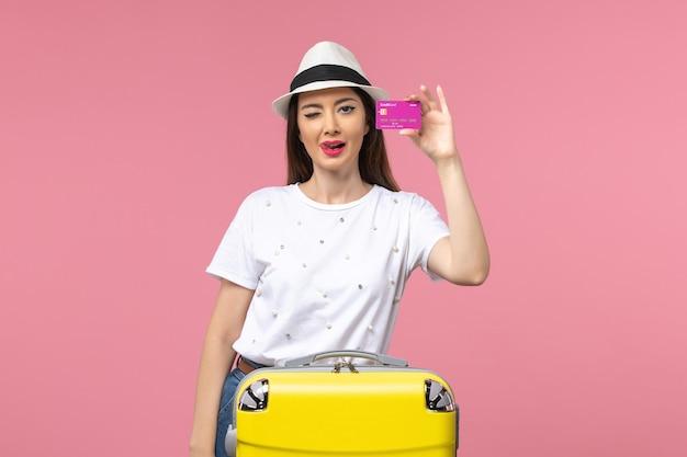 Vista frontal joven mujer sosteniendo tarjeta bancaria en pared rosa viaje viaje mujer dinero
