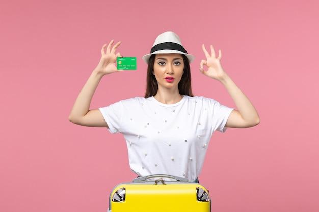 Vista frontal joven mujer sosteniendo una tarjeta bancaria en la pared rosada mujer de emociones de viaje de verano