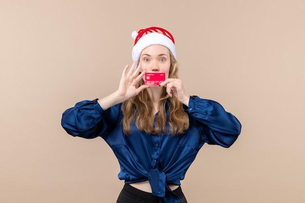 Vista frontal joven mujer sosteniendo una tarjeta bancaria roja en el piso rosa vacaciones navidad dinero foto año nuevo emoción