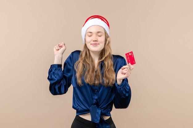 Vista frontal joven mujer sosteniendo tarjeta bancaria roja sobre fondo rosa navidad dinero foto vacaciones año nuevo emociones